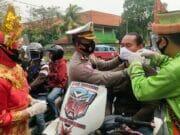 Gunakan Baju Adat di Jalan Raya, Polisi Bagikan 2 Ribu Masker ke Pengendara